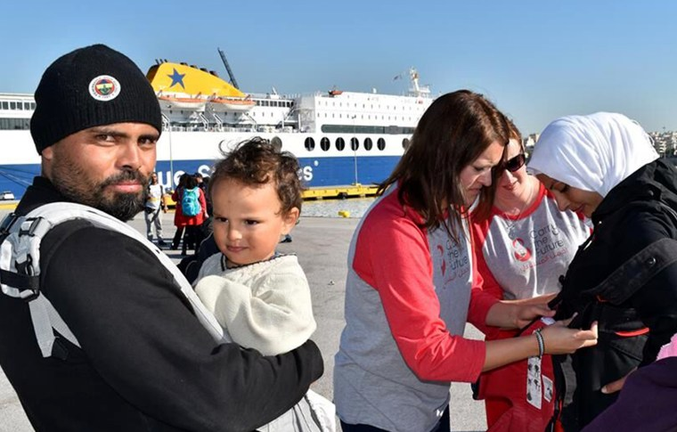 More than 9,000 refugees arrive on Greek shores daily, and 30 percent of them are children. Fleeing violence and forced from their homes, some families will walk hundreds of miles to find safety in Europe. Here, Carry The Future volunteers help fit refugees with baby carriers.