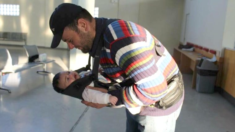 A father adjusts his one-month-old daughter in a donated baby carrier. His baby was born in Lebanon, and he said the family was fleeing Syria because it was no longer safe to raise. Even though baby-wearing is not prevalent in Syrian culture, many of the men like to be in charge of carrying the baby, as they have been leading the family through dangerous situations.