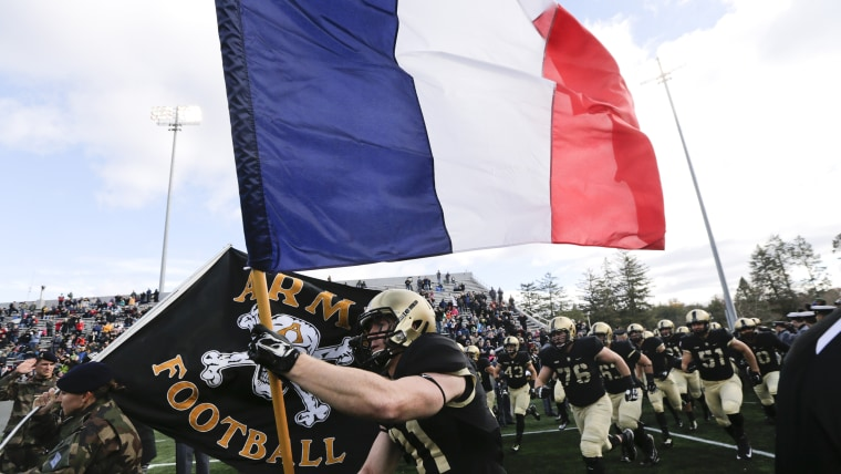 Army defensive back Caleb McNeill carries the flag of France onto the field before an NCAA college football game against Tulane, Saturday, Nov. 14, 2015, in West Point, N.Y.