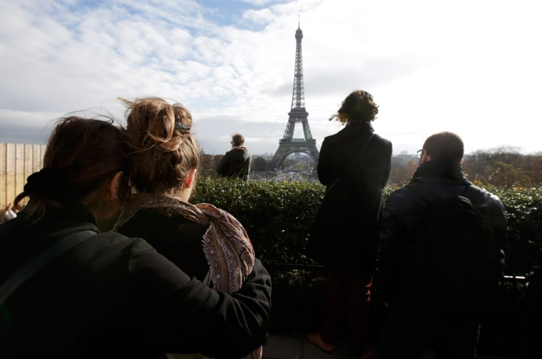 Image: People observe a minute of silence at the Trocadero in front the Eiffel Tower to pay tribute to the victims of the series of deadly attacks on Friday in Paris