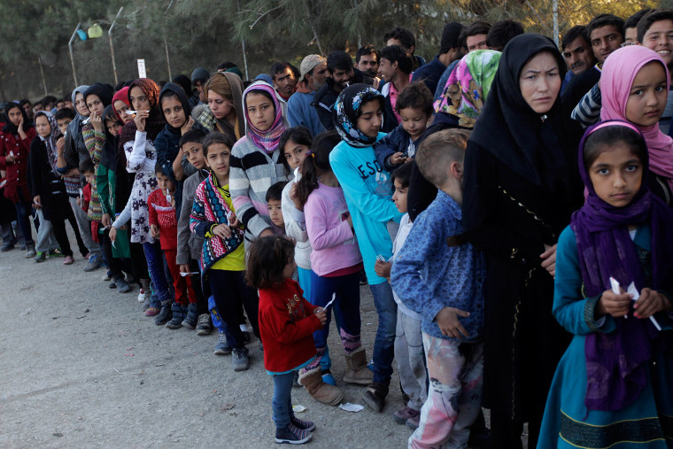 Image: Migrants wait in line to get food in a reception center