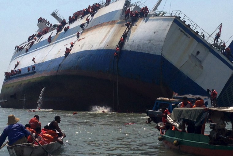 Image: Passengers climb down the side of the ferry KM Wihan Sejahtera as it capsizes in Tanjung Perak port, Surabaya