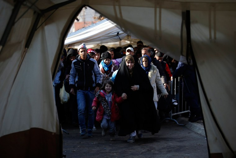Image: Migrants walk into a tent to register with the police