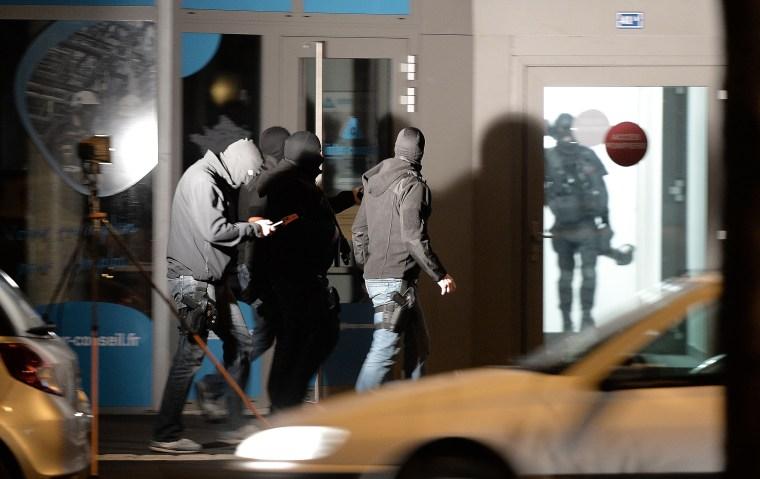 Image: Policemen walk along a building