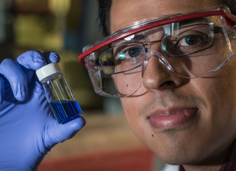 Lead author Victor García-López holds a vial containing millions of nanosubmarines.