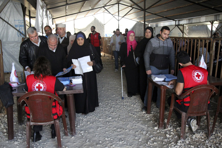 Image: Syrian refugees line up to receive aid for the winter from the UN refugee agency (UNHCR) in Tripoli, northern Lebanon
