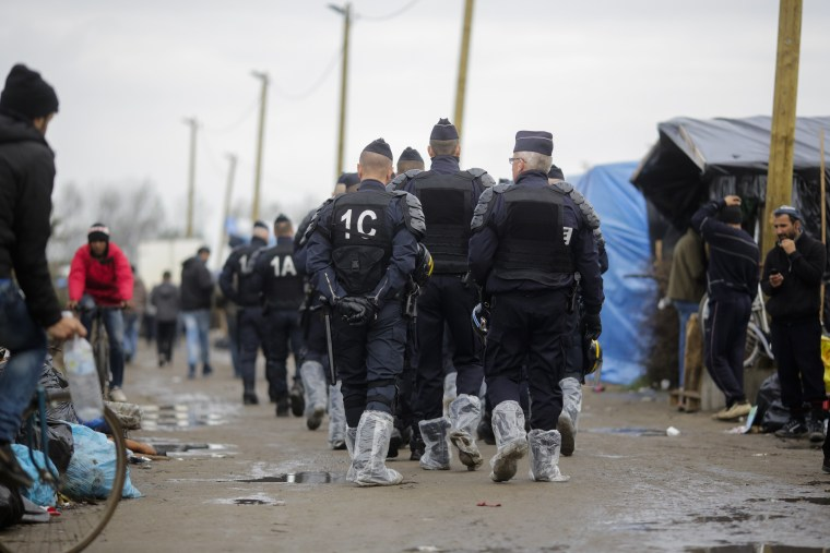 """Image: Police patrol """"The Jungle"""" camp in Calais, France, on Nov. 4"""