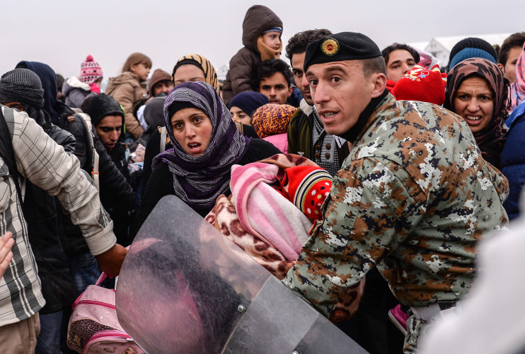 Image: A Macedonian soldier tries to controls refugees at the border on Nov. 20.