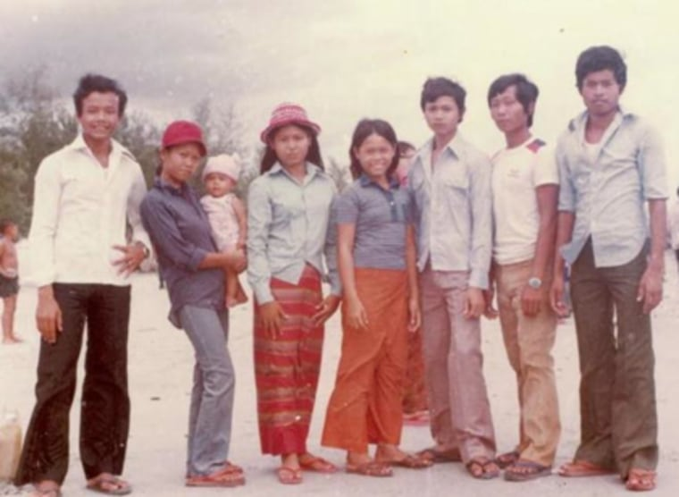 Lundy Khoy (baby on left), was born in a refugee camp in Thailand. This photo shows her with her her father (far left), mother (holding Lundy), and their brothers and sisters at the camp.