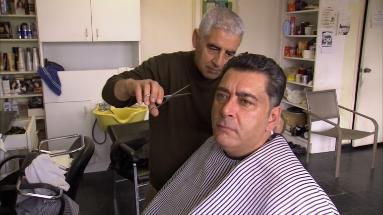 Hicham Diwal sits for a haircut in Dearborn, Mich. Diwal immigrated to the U.S. three decades ago.