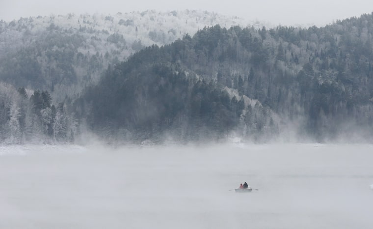 Image: A man and a woman travel in a rowboat along the Yenisei River through a frosty fog in the Taiga district, outside the Siberian city of Krasnoyarsk, Russia