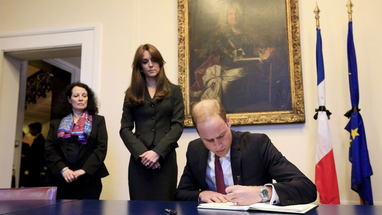 Image: Britain's Prince William, watched by Kate, the Duchess of Cambridge and French Ambassador to London Sylvie Bermann, signs the book of condolences for the victims of the attacks in Paris, at the French Embassy, Knightsbridge, London