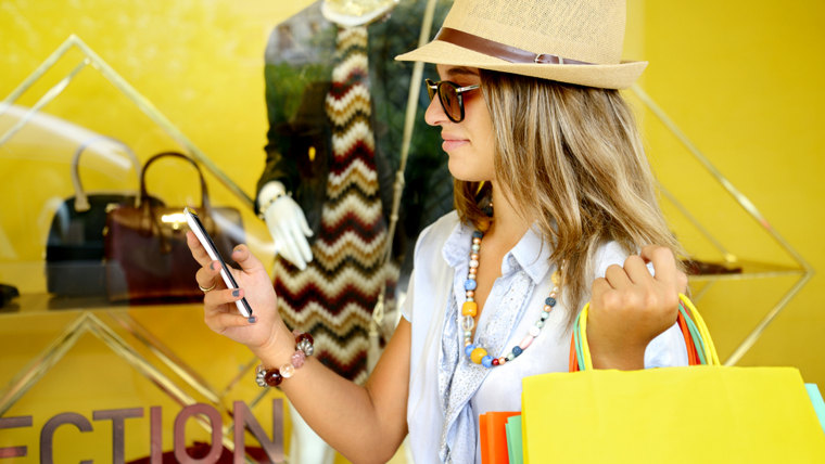 Young woman with smartphone and shopping bags; Shutterstock ID 338792711; PO: today.com