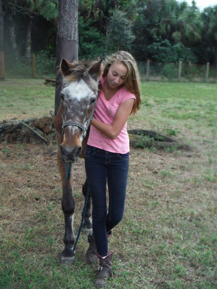 A girl hugs an old horse named Barney the day before he passed away.