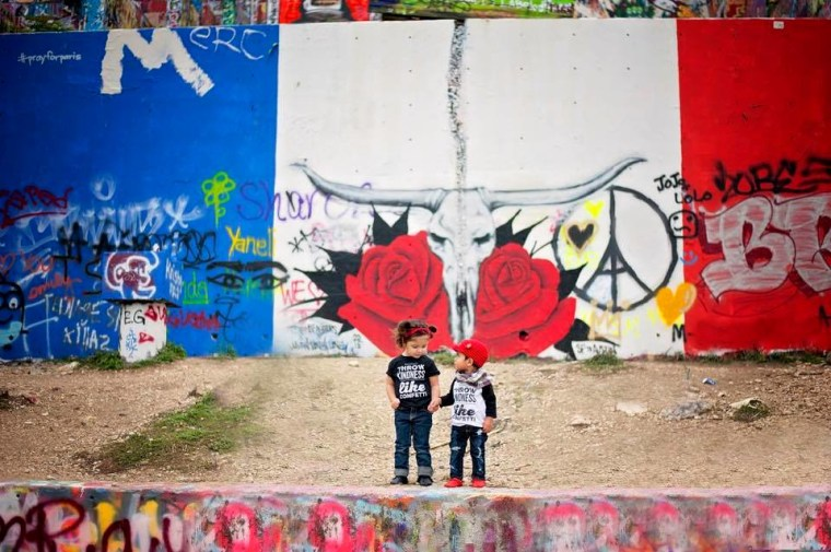 """My 2-year-old Milah & her little friend showing love from Austin, Texas. This mural was painted last Saturday night. Their shirts read, 'Throw kindness like confetti.'"""