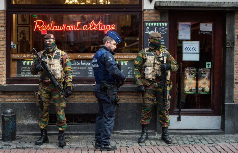 Image: A Police officer and soldiers stand guard  in the 'Rue des Bouchers' street