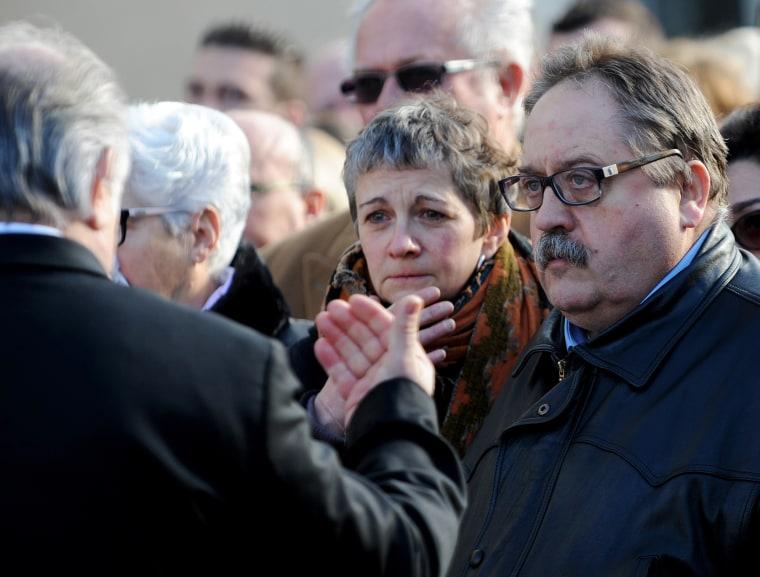 Image: An attendant speaks to Sylvie Lieffrig-Petard and her husband Erick Lieffrig-Petard