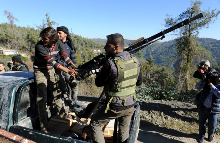 Image: Syrian Turkmen fighters are seen with an anti-aircraft artillery weapon near the northern Syrian village of Yamadi, near the Turkish-Syrian border, Syria