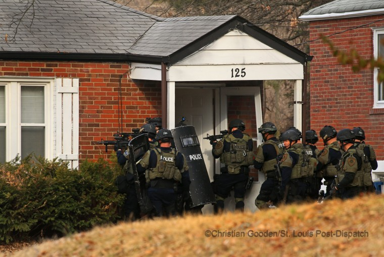 After months of peaceful protests and the sense of calming in the community, tensions rose again when a police officer was shot during a large protest outside the Ferguson police department. A manhunt ensued. The following day, a police tactical unit enters a home in the 100 block of  Dade Ave. in Ferguson in March 2015, in an unsuccessful search. Withing days, police eventually caught the individual responsible without incident and announced that his motives had nothing to do with the protests. The shooter's intended target was someone he knew who was outside the police station.