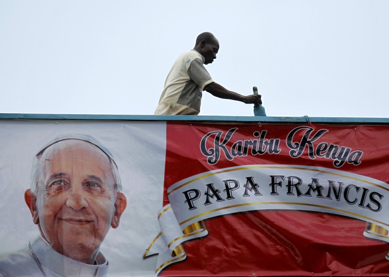 Image: A volunteer paints the wall near a banner of Pope Francis at at the University of Nairobi grounds ahead of the Papal Mass in Kenya's capital Nairobi