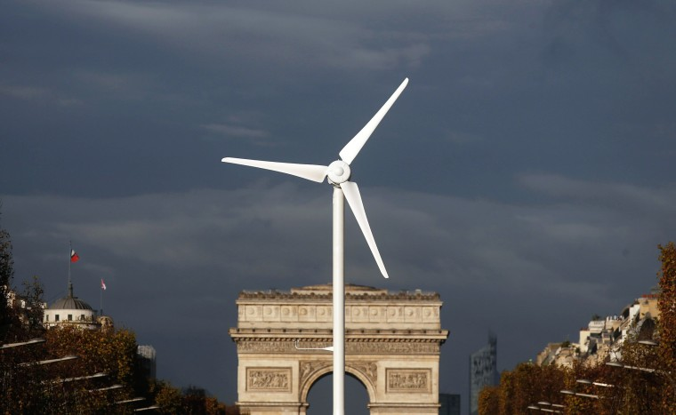 Image: A power-generating windmill turbine is seen in front of the Arc de Triomphe