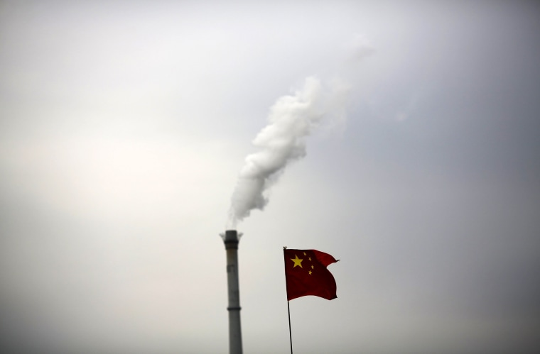 Image: File photo of China's national flag being seen in front of a chimney of a cogeneration plant in Beijing