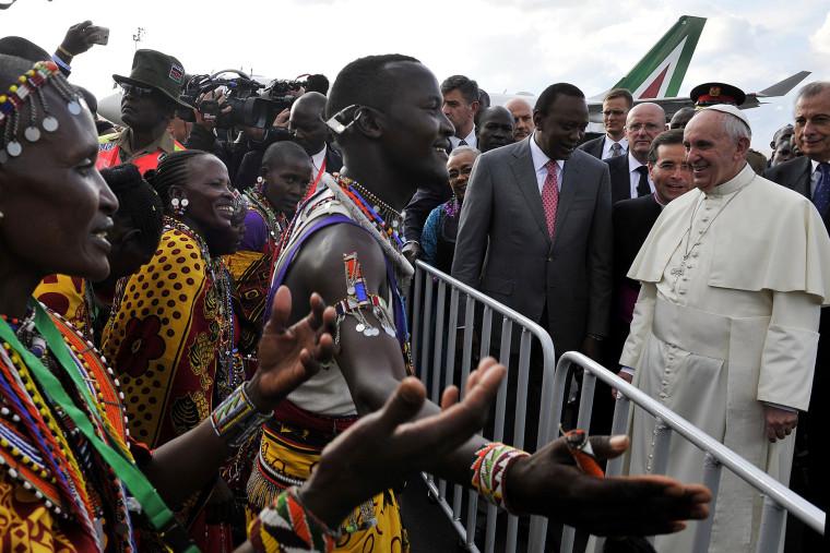 Image: Pope Francis stands beside Kenya's President Uhuru Kenyatta as they watch traditional dancers
