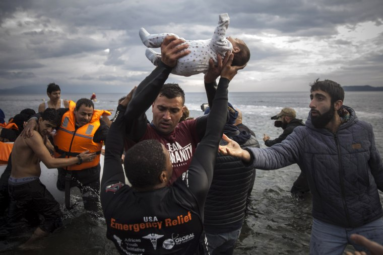 Image: A volunteer holds up a baby as others help migrants and refugees to disembark from a dinghy