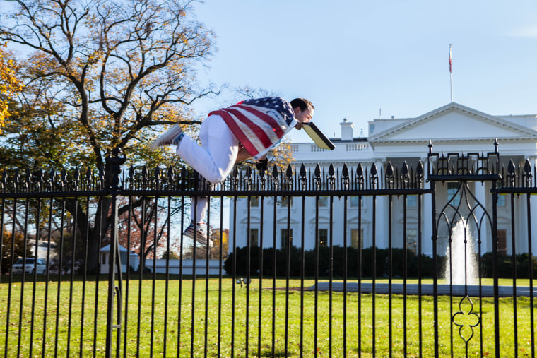 A man draped in American flag climbs over the fence surrounding the White House grounds, Thursday. Nov. 26, 2015.