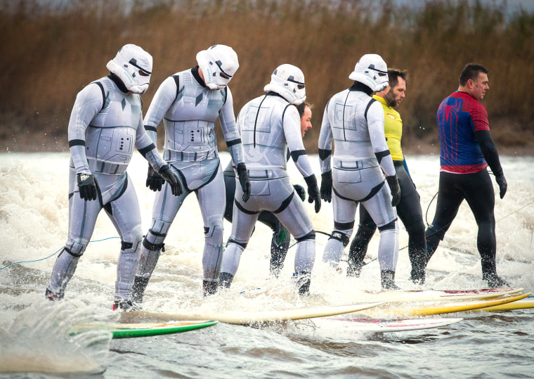 Surfers dressed as Star Wars Stormtroopers ride the Severn Bore in Gloucestershire.