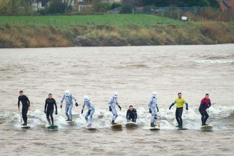 Surfers dressed as Star Wars Stormtroopers ride the Severn Bore on the River Severn in Gloucestershire, England.