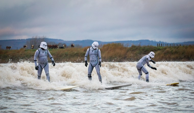 Surfers dressed as Star Wars Stormtroopers ride the Severn Bore.