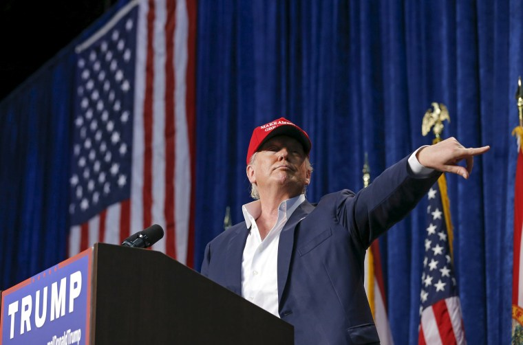 Image: U.S. Republican presidential candidate Donald Trump motions for security to remove a person from his rally in Sarasota, Florida