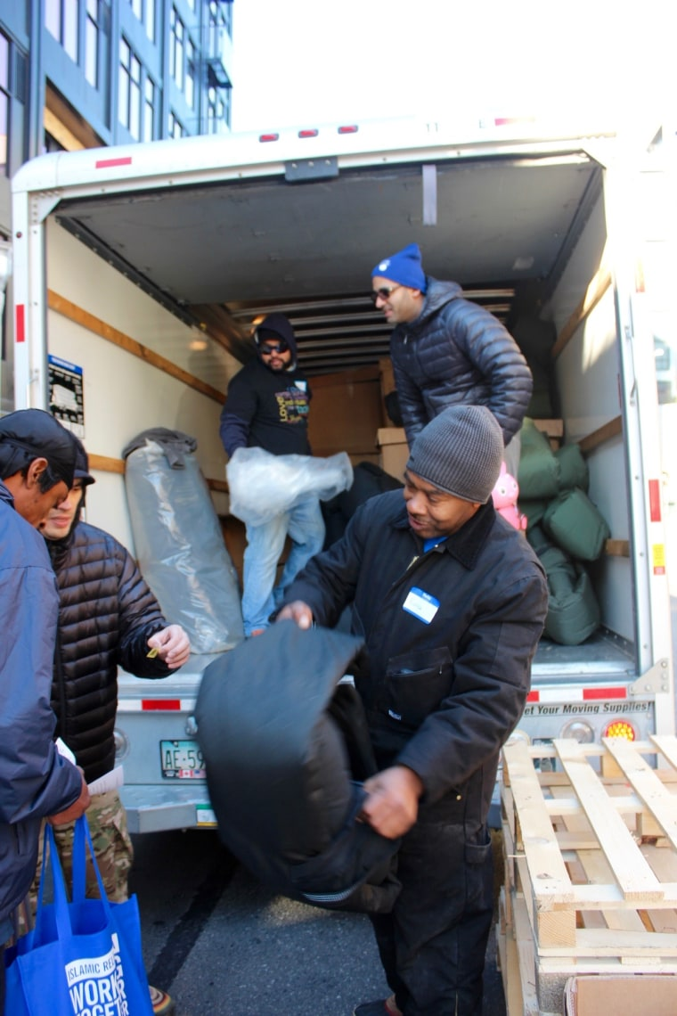 Volunteers unload a truck of special coats that also serve as sleeping bags.