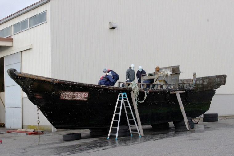 Image: Coast guard officials investigating a wooden boat