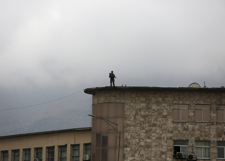 Image: An Afghan security personnel keeps watch atop a building