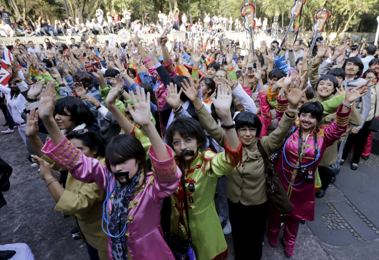 Image: People wave as they take part in an attempt to set a Guinness World Record for the largest number of people dressed as members of the British band The Beatles at a park in Mexico City, Mexico