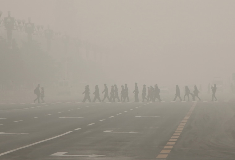 Image: Pedestrians and policeman cross the street at a crosswalk at the Tiananmen Square during a heavily polluted day in Beijing