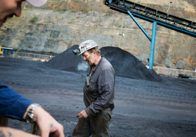 Image: Foreman John Dillon walks past piles of coal