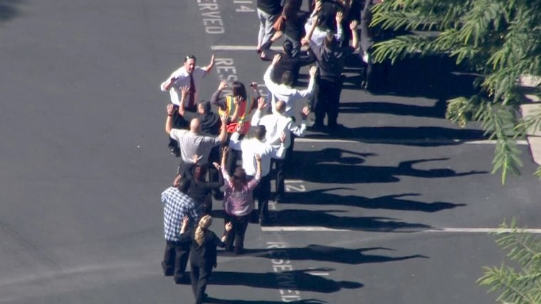 People being lead away from the Inland Regional Center.