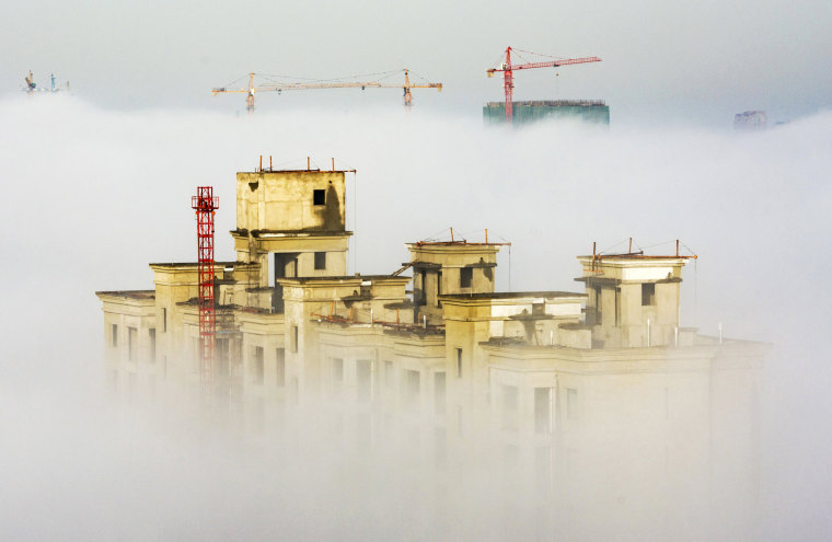 Image: Cranes and residential buildings under construction are seen among thick fog in Anyang