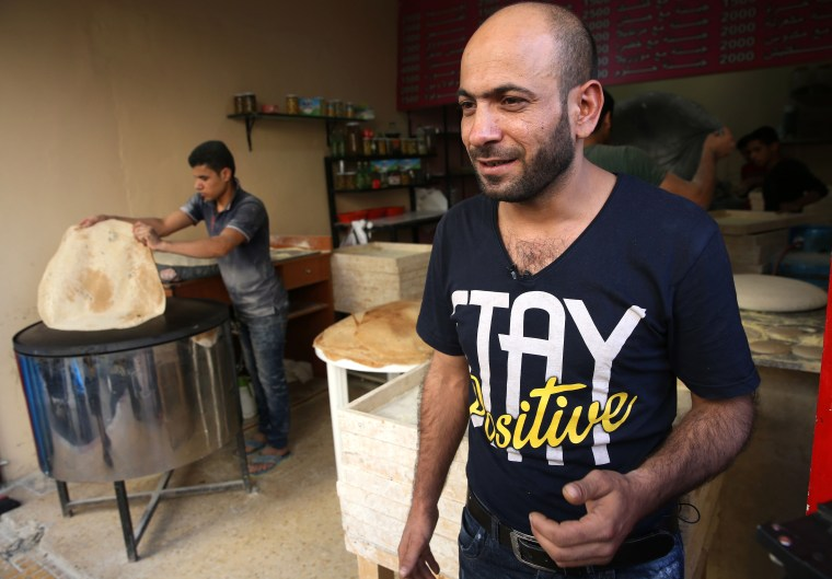 Image: Abdul Halim al-Attar stands outside his bakery in Beirut, Lebanon.