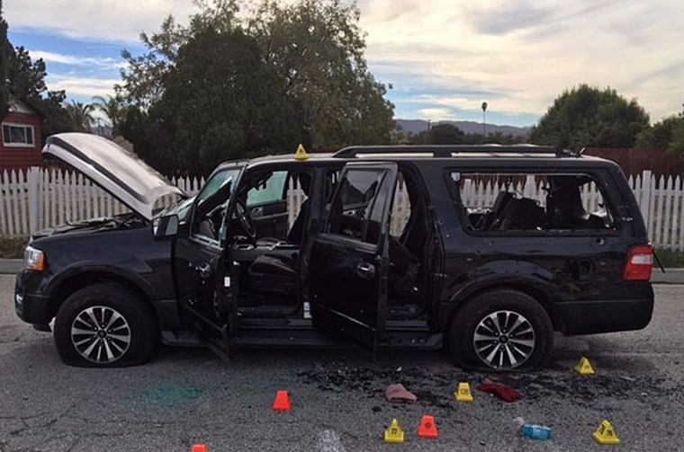 A bullet-riddled black SUV sits at the scene of a shootout between police and the couple who went on a rampage at the Inland Regional Center in San Bernardino, California.