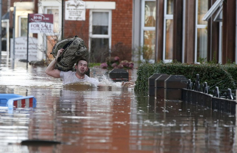 Image: A local resident carries a bag as he wades through flood water on a residential street in Carlisle, Britain