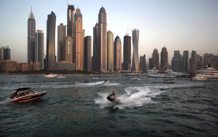 Image: People use recreational vehicles opposite the Marina district of Dubai