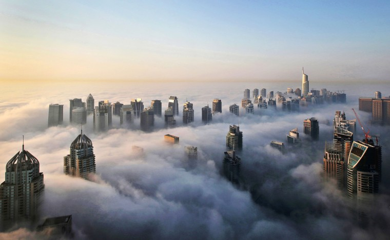 Image: A thick blanket of early morning fog partially shrouds the skyscrapers of the Marina and Jumeirah Lake Towers districts of Dubai