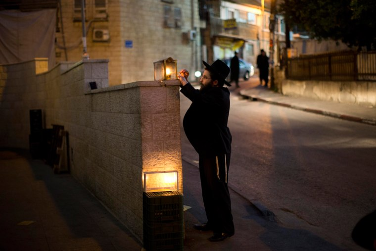 Image: An Ultra-Orthodox Jewish man lights a Hanukkah candle outside his house during the Jewish holiday of Hanukkah