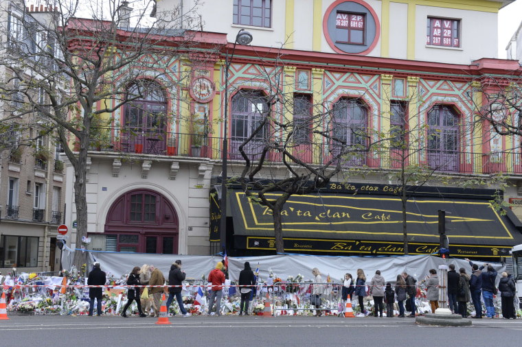 Image: People gather to lay flowers at a makeshift memorial