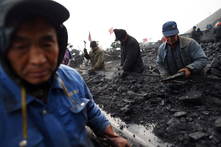 Image: Workers sort coal on a conveyor belt, near a mine in Datong, China