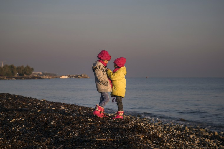 Image: Two sisters from Syria play on a beach near the town of Mytilene after crossing a part of the Aegean sea